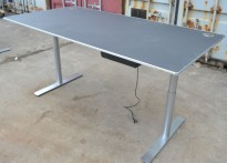 Skrivebord fra Holmris med elektrisk hevsenk, sort med kant i aluminium, satinert stål understell, 200x100cm, pent brukt