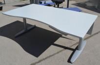 Lekkert skrivebord i Kinnarps T-serie i lys grått, 160cm bredde 90cm dybde m/ magebue, pent brukt