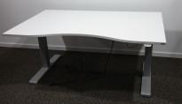 Skrivebord med elektrisk hevsenk i hvitt / grått understell fra Kinnarps, P-serie, 140x90cm med mavebue, pent brukt