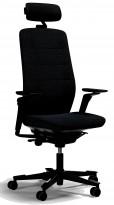 Kontorstol fra Kinnarps: Modell Capella i sort stoff, høy rygg, armlener, nakkepute i sort skinn, sort kryss, pent brukt