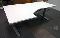 Skrivebord med elektrisk hevsenk i hvitt fra Kinnarps, 180x120cm, ventresløsning, pent brukt understell med ny plate