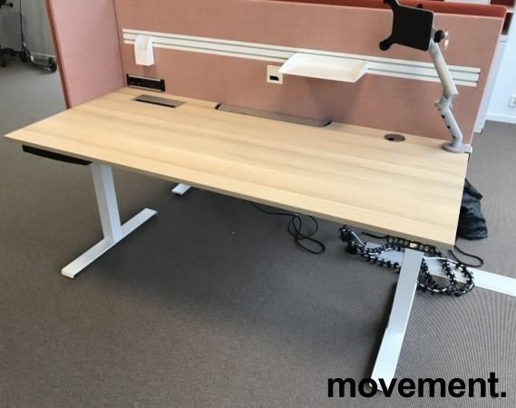 Skrivebord elektrisk hevsenk, Kinnarps, eik laminat bordplate, hvitt understell, rosa vegg, 180x80cm, pent brukt bilde 3