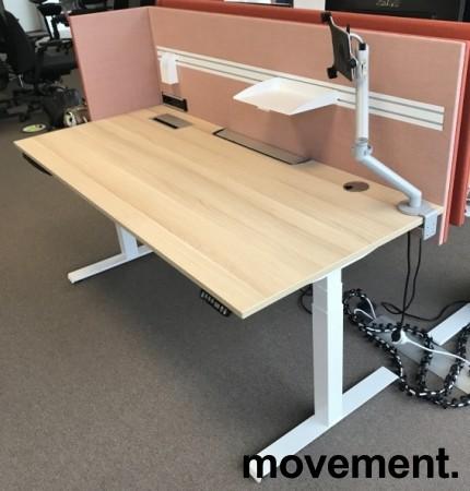 Skrivebord elektrisk hevsenk, Kinnarps, eik laminat bordplate, hvitt understell, rosa vegg, 180x80cm, pent brukt bilde 1