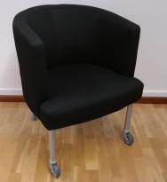 Kinnarps Arriba loungestol i sort stoff med hjul på to ben, pent brukt
