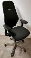 Kontorstol: Kinnarps Plus 8 i sort stoff, gel-armlener, mørkegrått kryss, høy rygg, pent brukt