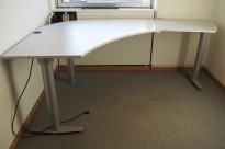 Kinnarps elektrisk hevsenk hjørneløsning skrivebord i lys grå, 220x140cm, sving på høyre side, T-serie, noe slitasje i plater