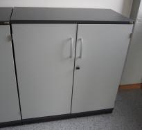 Skap fra Kinnarps i mørk grå med dører i lys grå, E-serie, 85cm høyde, 2 permhøyder, pent brukt.